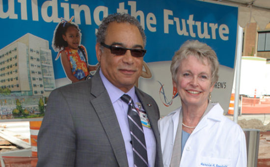 George Brown, M.D., FACP, Legacy Health president and chief executive officer and Marcia H. Randall, with her newly presented white coat embroidered with the new name of the new home: Randall Children's Hospital at Legacy Emanuel.