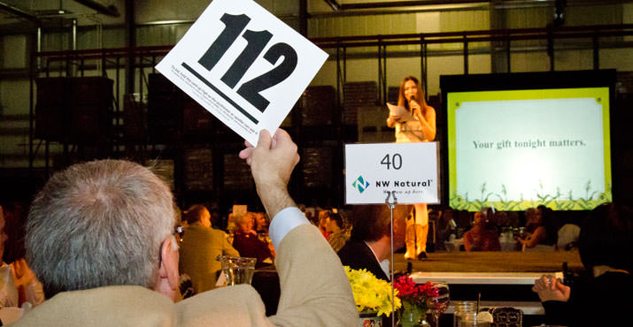 "Gary Bauer, director of government and community affairs, NW Natural, raises paddle during Special Appeal, led by auctioneer Johnna Wells, at ""Home Grown,"" Oregon Food Bank's annual gala fundraiser, Oct. 15, 2011."