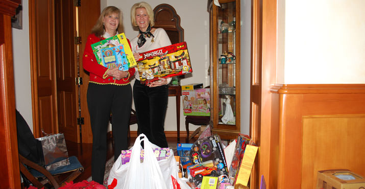 Jill Inskeep and Susie Porter pose with the Toy and Joy gifts brought by guests