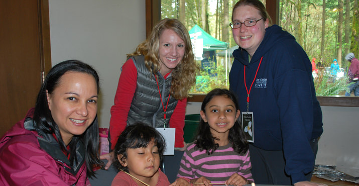 Melarie DeSelvia with her daughters Malia and Piriya get help from Derek Mellinger and Laura Markel