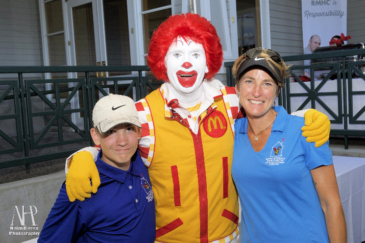Wade Chosvig, a former Ronald McDonald House guest, poses with CEO Jessica Jarratt Miller and Ronald McDonald. Wade spent the day on the links showing off his incredible golf skills and helped announce this year's tournament winners.