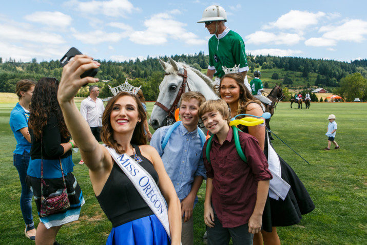Miss Oregon 2016, Alexis Mather and Miss Oregon Outstanding Teen 2016, Abigail Hoppe, pose for a selfie with two young guests and polo players on the field.